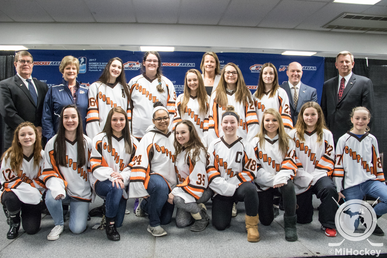 Members of the Compuware girls' 12U and 16U teams pose with USA Hockey's Dave Ogrean, MAHA's Jean Laxton, USAH's Reagan Carey, Plymouth Township supervisor Shannon Price and USAH president Jim Smith. (Photo by Michael Caples/MiHockey)