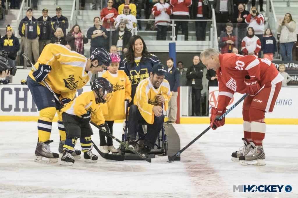 Scott Matzka, joined by his family at center ice of Yost Ice Arena, drops the puck in a ceremonial puck drop before the Wolverines' alumni squad took on the Red Wings' alumni team. (Photo by Michael Caples/MiHockey)